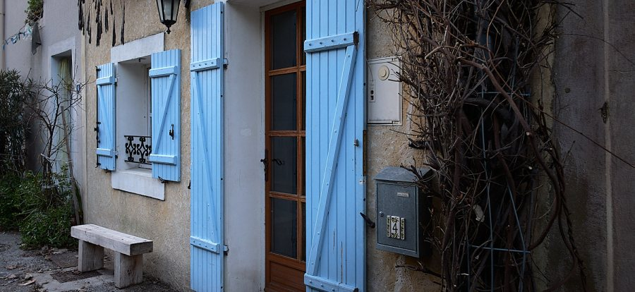 Blue door and window shades in the town of Malaucene at the foot of the Mont Ventoux