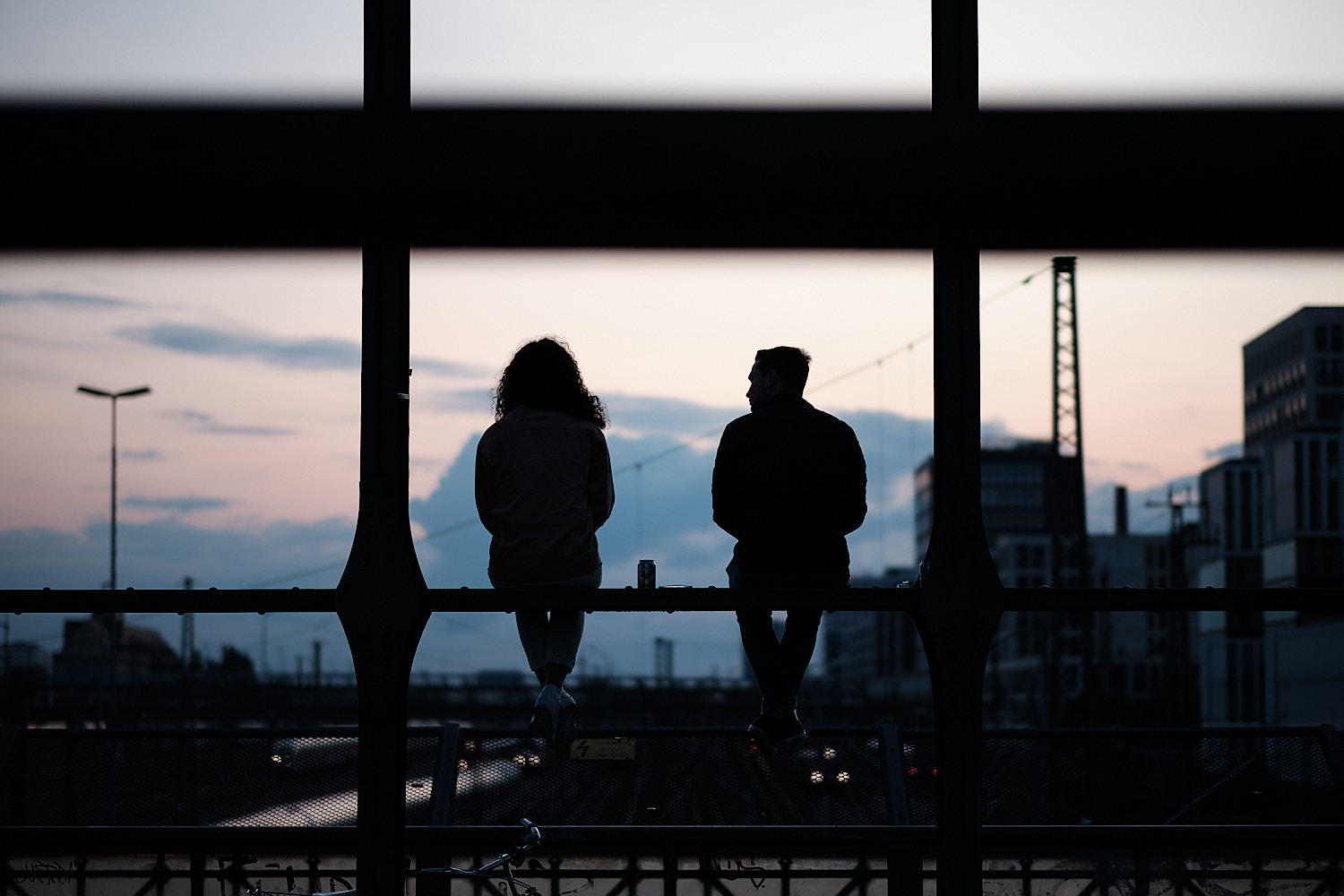 A couple chat perched over a beam at the bridge. In the background the sunset blue sky sets them as dark profiles.