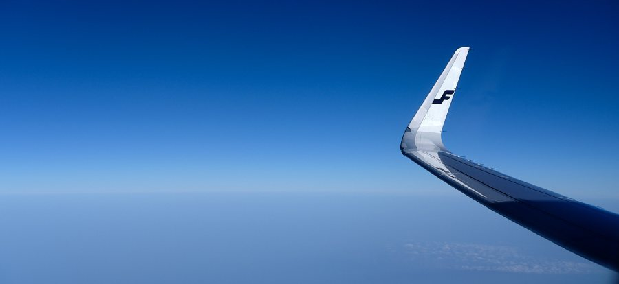 Airplane wing with Finnair flagshield on a blue sky backdrop over the north sea