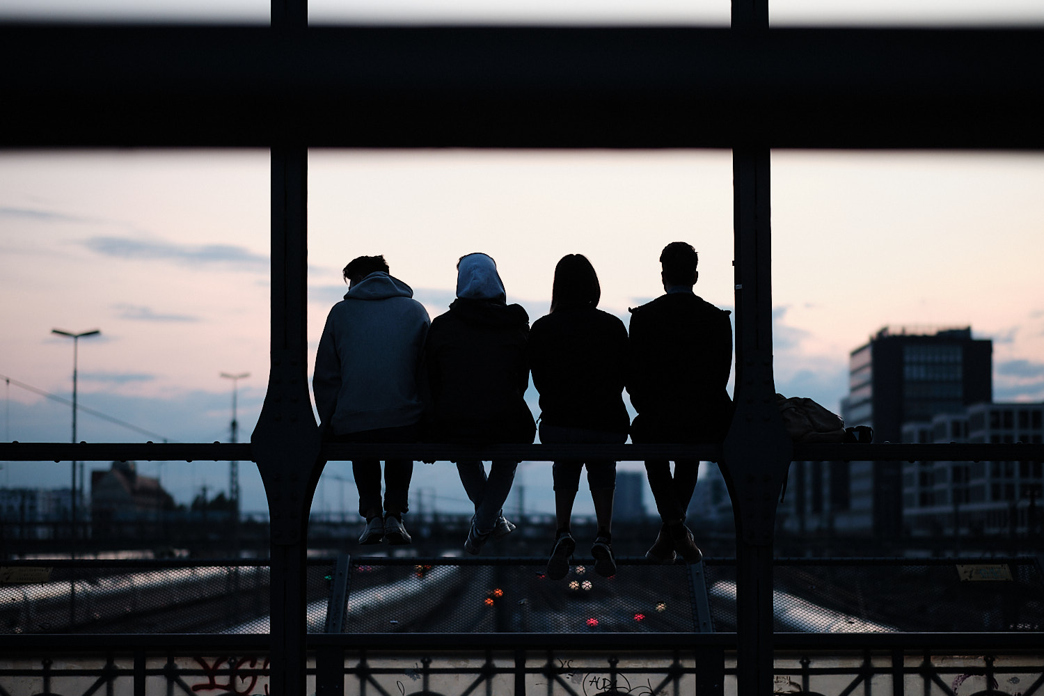 A group of four young boys chat perched over a beam at the Hackerbrücke bridge. In the background the sunset blue sky sets them as dark profiles.