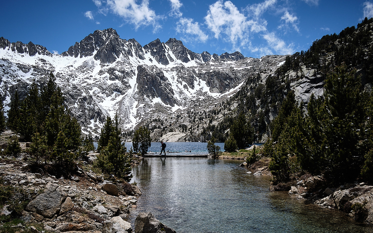Six-days hike around the Parc Nacional d'Aiguetortes i Estany de Sant Maurici in the central Pyrenees. View of deep blue lakes and snowed mountains.