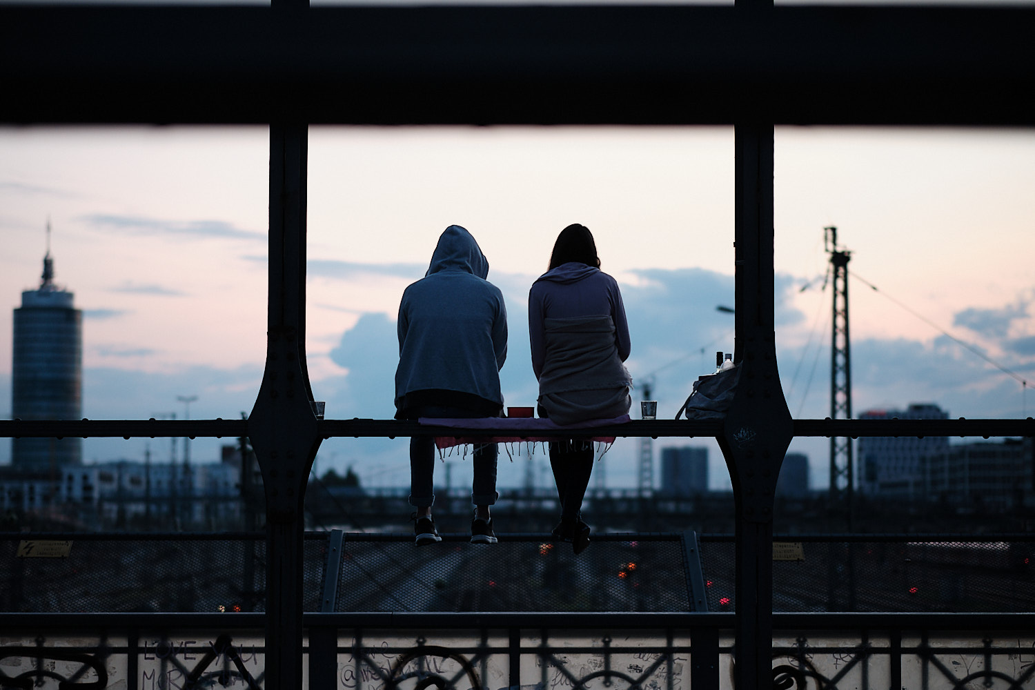 A couple chat perched over a beam at the Hackerbrücke bridge facing the west sky. In the background the sunset blue sky sets them as dark profiles.