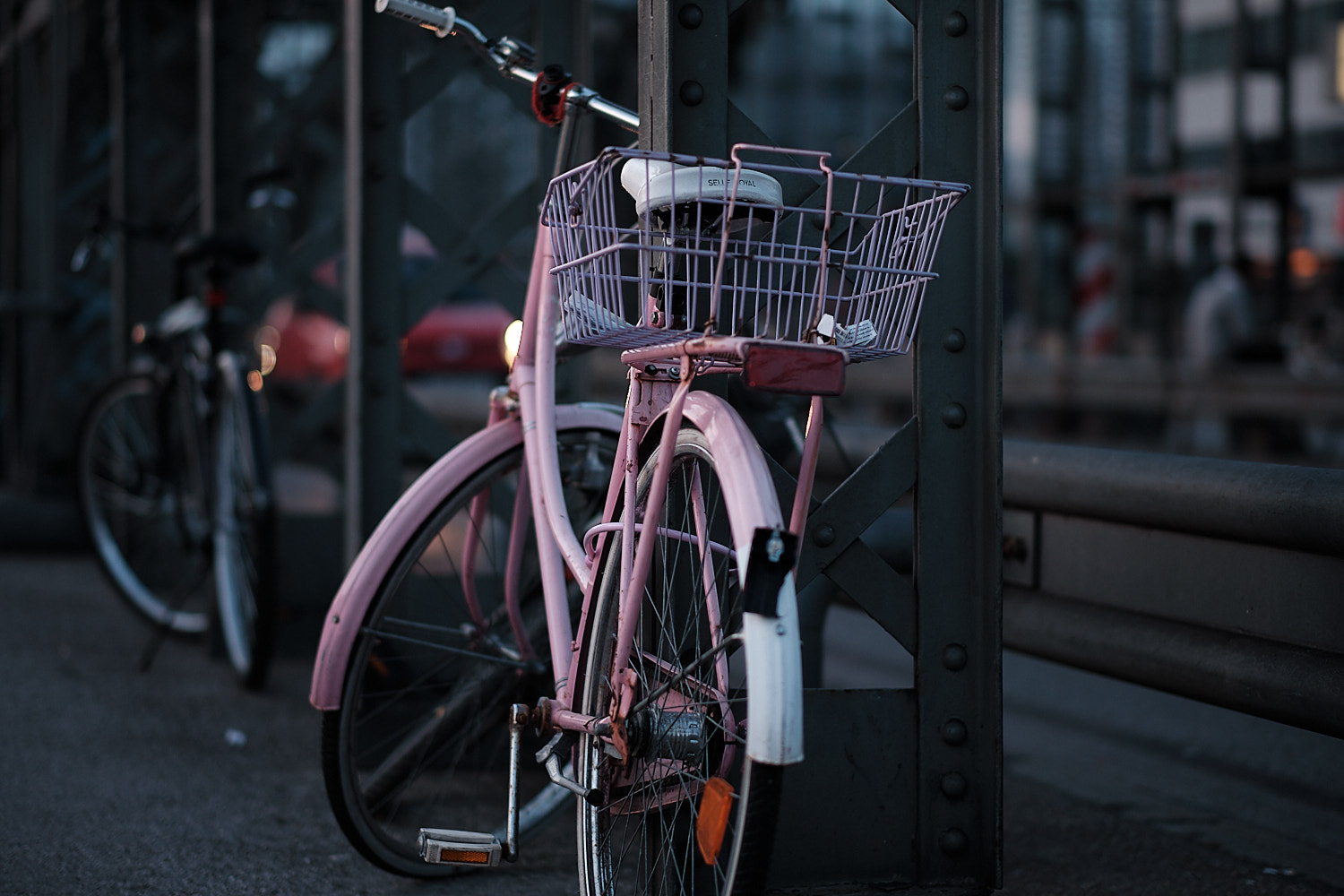 A view of the east side of the Hackerbrücke bridge from the south side in the late afternoon blue hour and a pink bicycle locked to a pillar.
