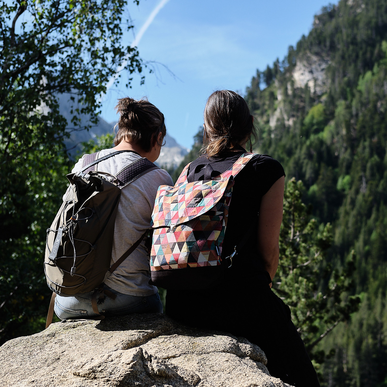 Two young ladies tourists sitting atop a stone during a walk around Estany de Sant Maurici, Pyrenees, Cataluña, Spain