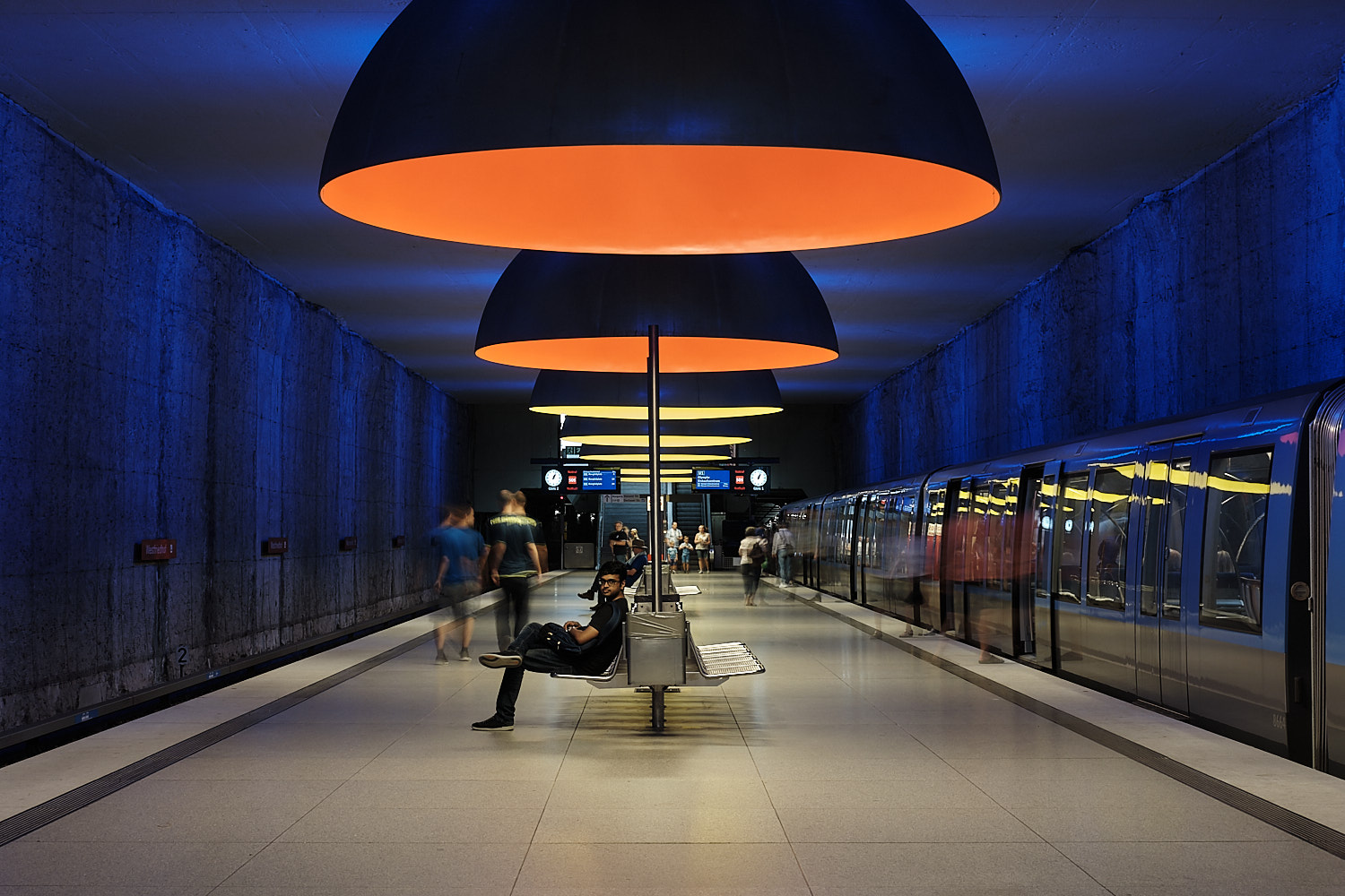 Westfriedhof long exposition U-Bahn stationed passengers moving in. Orange and yellow ceiling hanging lamps from Ingo Maurer