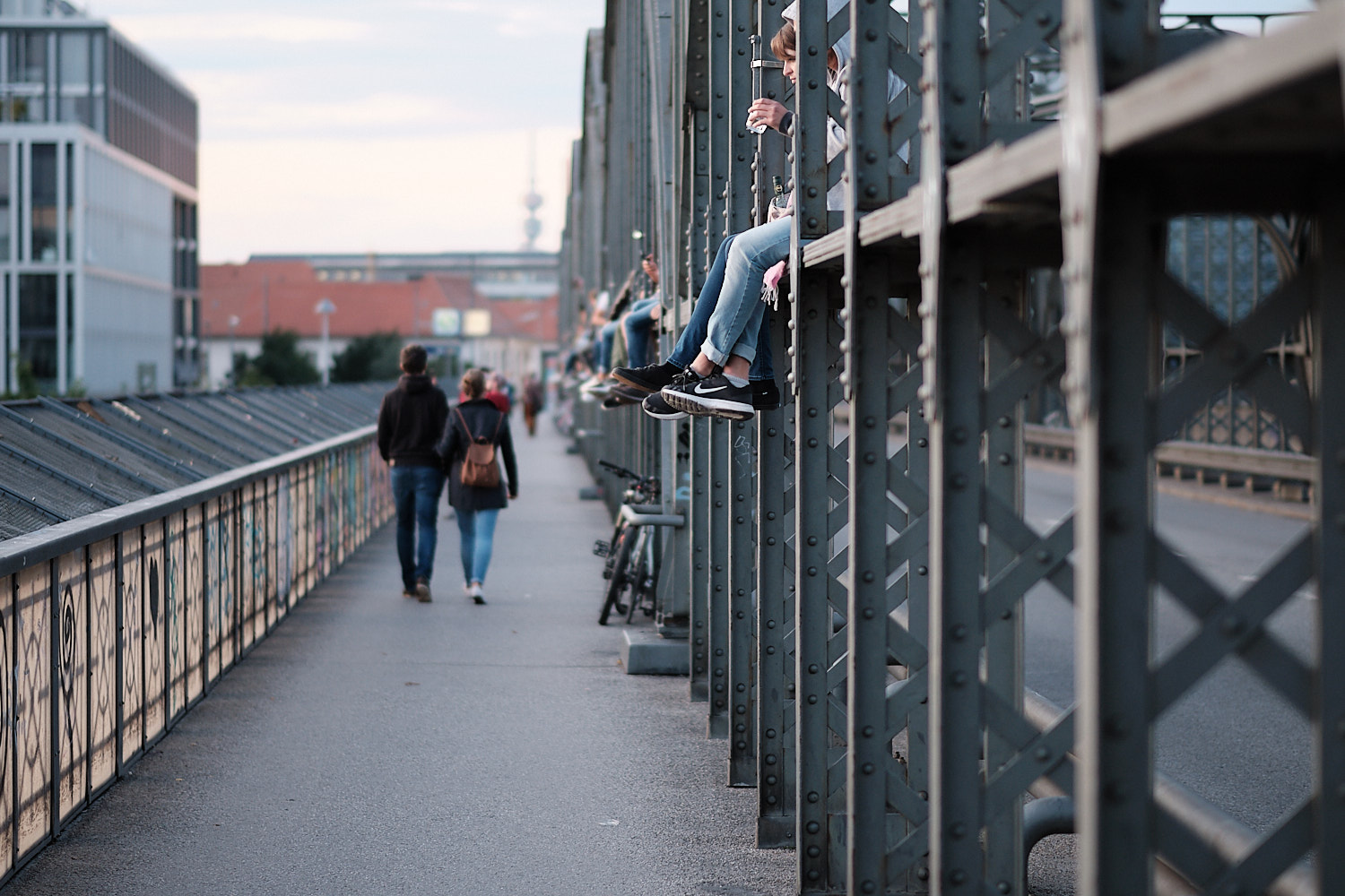 A view of the east side of the Hackerbrücke bridge from the south side in the afternoon. Many young people sitting over the bridge beams with swinging legs enjoying the sunset view