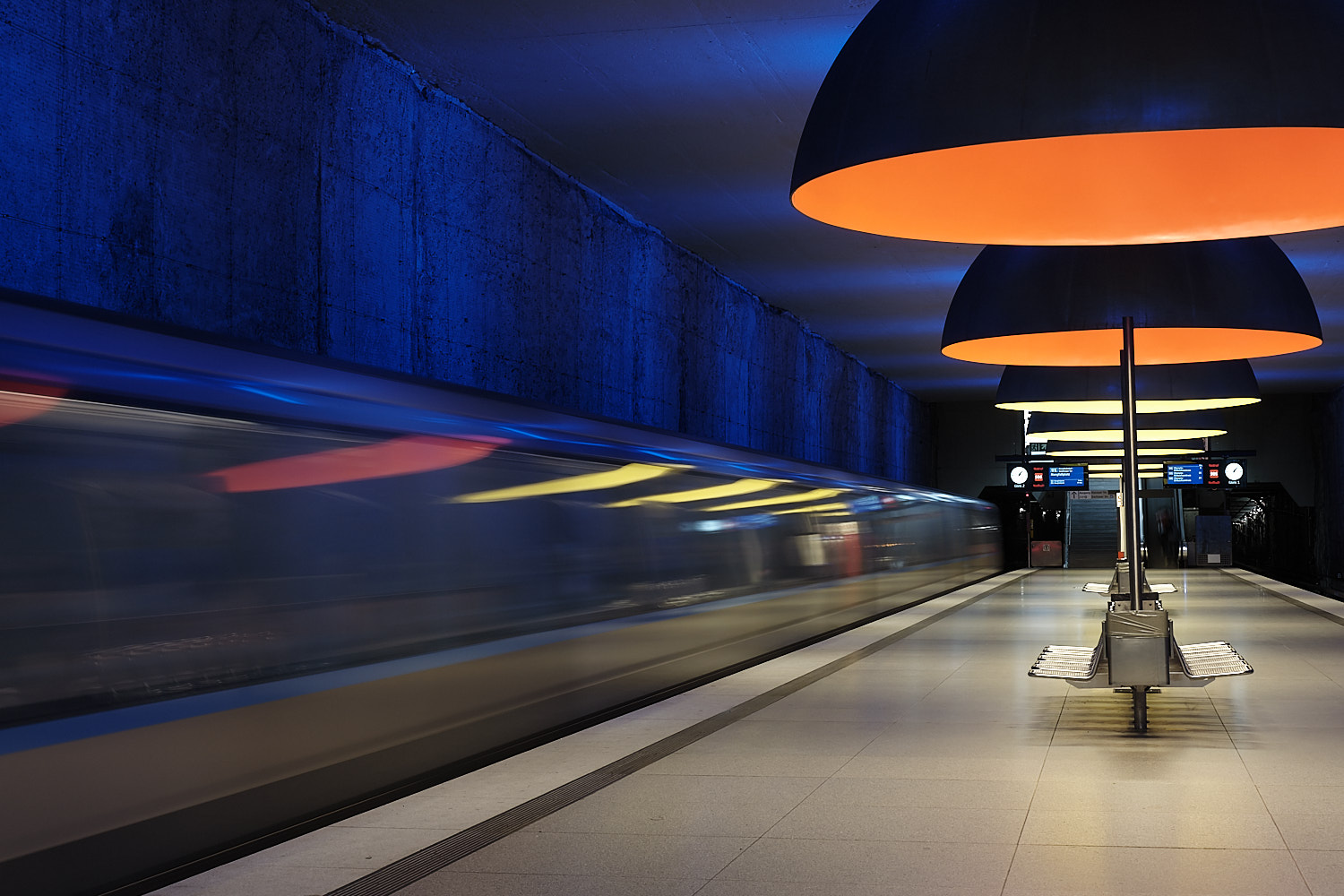 Westfriedhof long exposition U-Bahn departing station and platform is empty. Orange and yellow ceiling hanging lamps from Ingo Maurer