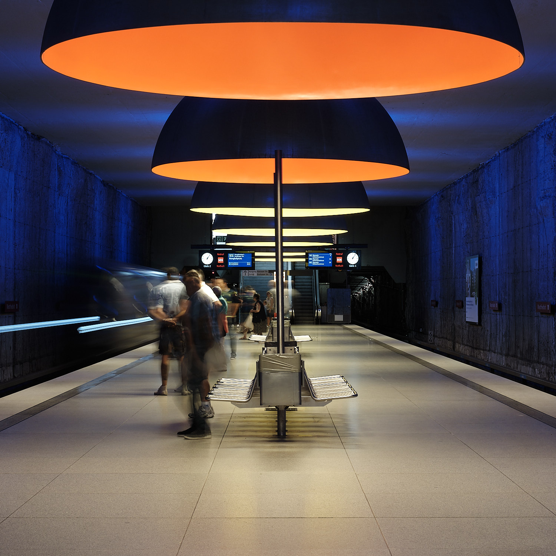 Westfriedhof long exposition U-Bahn entering station passengers waiting. Orange and yellow ceiling hanging lamps from Ingo Maurer