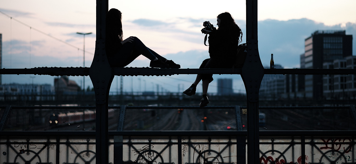 Two young ladies take photographs of themselves perched over a beam at the Hackerbrücke bridge. In the background the sunset blue sky sets them as dark profiles.