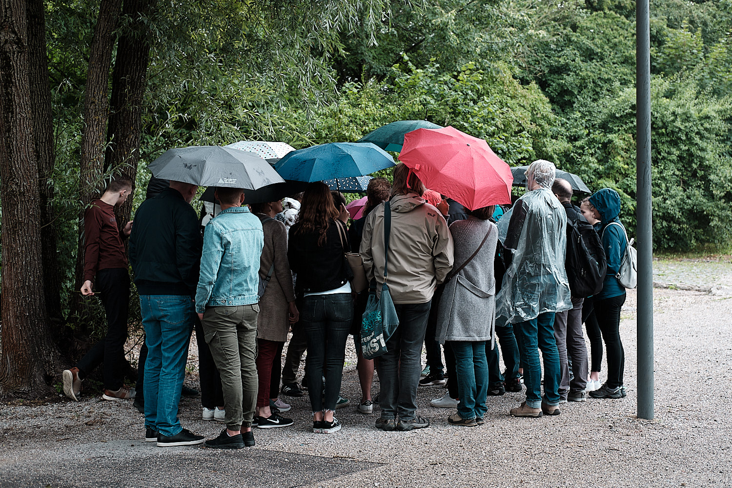 Historical site of the concentration camp of Dachau. Guided tour. Visitors gather under umbrellas around the guide.