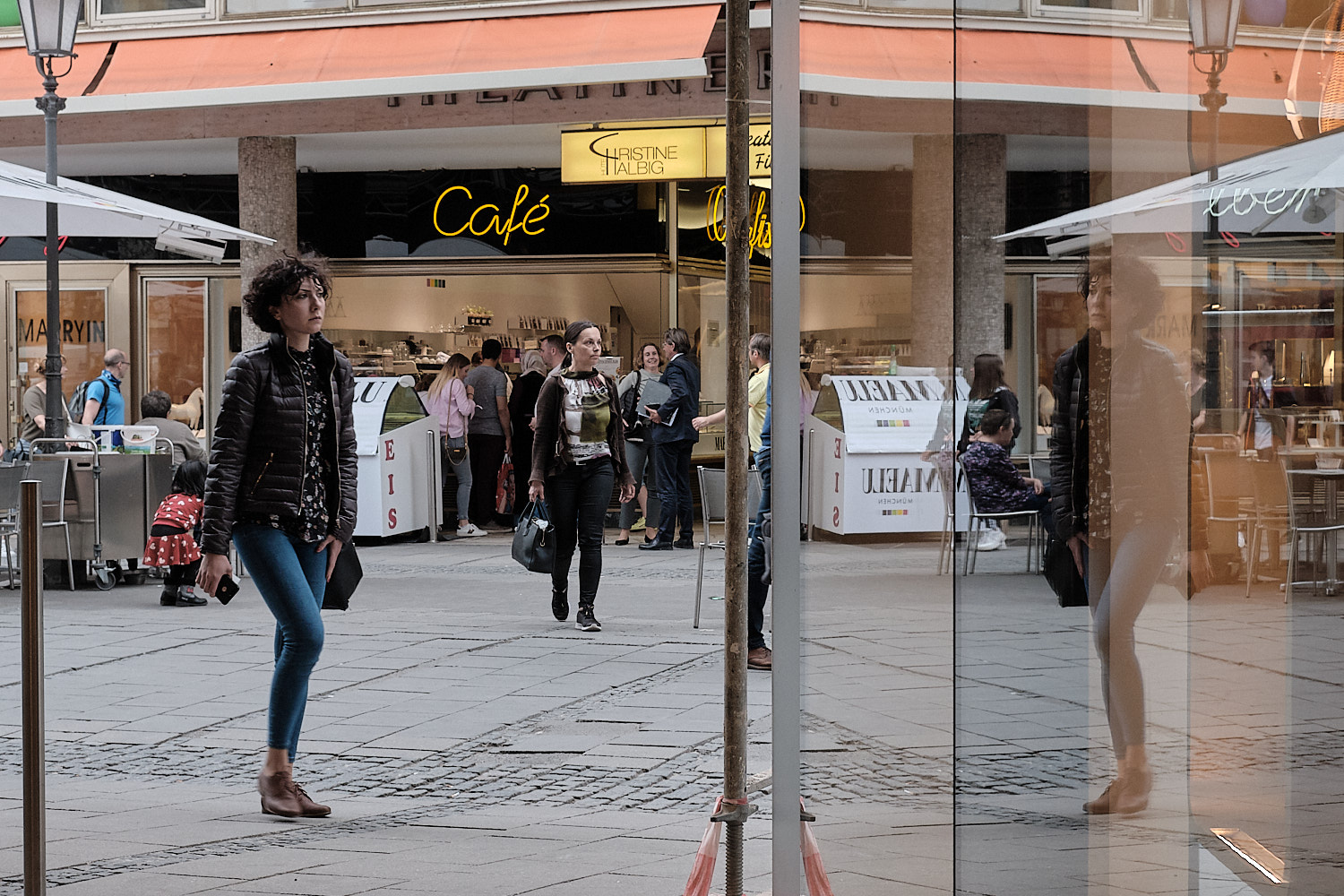 Bypassers and their reflexions in a shopping street in Munich