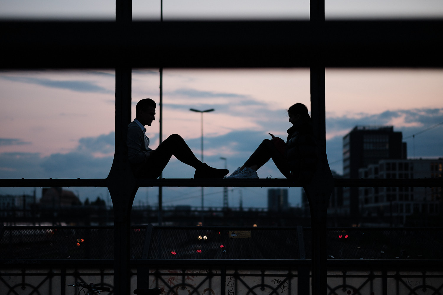 A couple chat and check their smartphones perched over a beam at the Hackerbrücke bridge. In the background the sunset blue sky sets them as dark profiles.