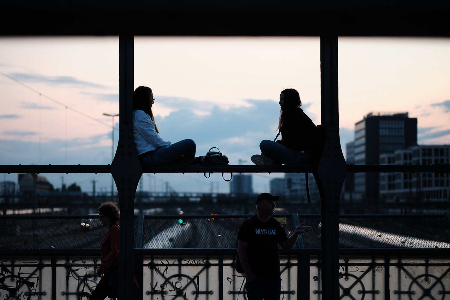 Two ladies chat perched over a beam at the Hackerbrücke bridge. In the background the sunset blue sky sets them as dark profiles.